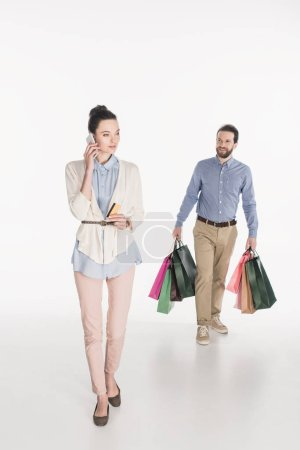 woman with credit card talking on smartphone while husband carrying shopping bags isolated on white