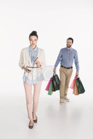 Photo for Woman with credit card and smartphone looking at camera while husband carrying shopping bags isolated on white - Royalty Free Image
