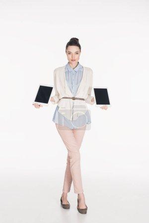 Photo pour Femme montrant des comprimés avec des écrans vierges en mains isolés sur blanc - image libre de droit