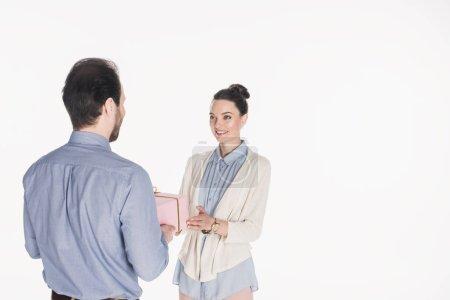 partial view of man presenting wrapped gift to smiling wife isolated on white