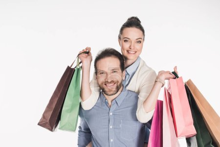 Photo for Happy woman with shopping bags and husband piggybacking together isolated on white - Royalty Free Image