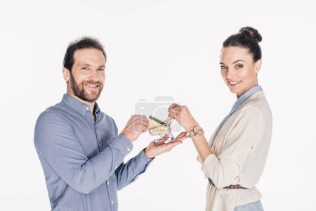 side view of smiling couple holding little shopping cart and credit card in hands isolated on white