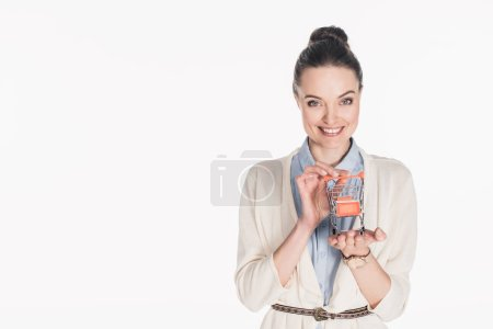 portrait of cheerful woman holding little shopping cart in hands isolated on white