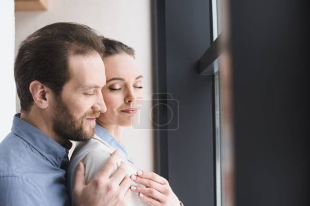 side view of smiling man hugging beautiful wife