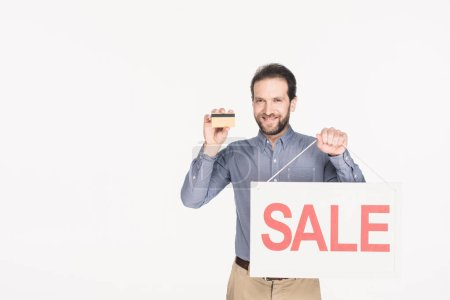portrait of smiling man with sale card and credit card in hands isolated on white