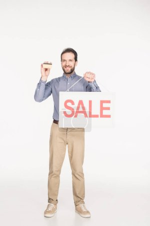 smiling man with sale card and credit card in hands isolated on white
