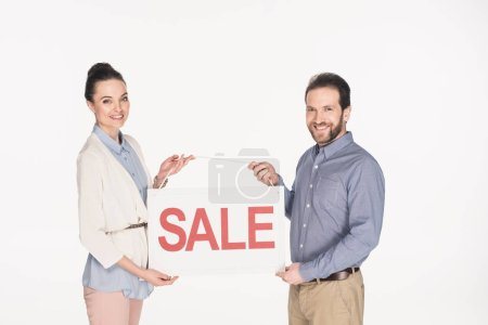 portrait of smiling couple holding sale banner isolated on white