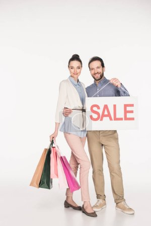 smiling couple with sale banner and shopping bags isolated on white