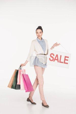 Photo pour Belle femme avec des sacs à provisions montrer signe de vente isolé sur blanc - image libre de droit