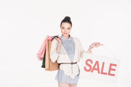portrait of woman with shopping bags showing sale sign isolated on white