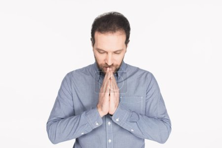 portrait of bearded man in shirt praying isolated on white
