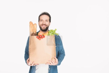 portrait of smiling bearded man with paper package with grocery isolated on white