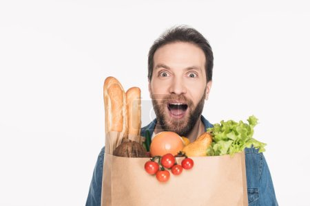 portrait of excited bearded man with paper package full of food isolated on white