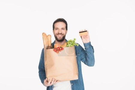 portrait of smiling man with credit card and paper package full of food isolated on white