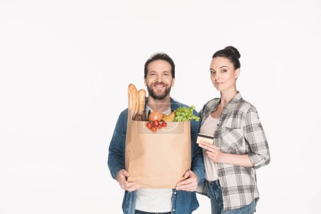 portrait of smiling couple with credit card and paper package with grocery isolated on white