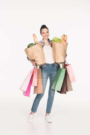 Photo for Cheerful woman holding paper packages with food and shopping bags in hands isolated on white - Royalty Free Image
