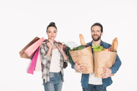 portrait of wife and husband holding shopping bags and paper packages full of food isolated on white