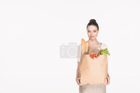 portrait of woman in apron holding paper package full of food isolated on white