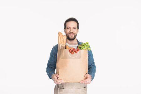 portrait of bearded man in apron with paper package with grocery isolated on white