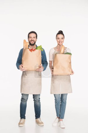 cheerful shop assistants in aprons holding paper packages with food isolated on white