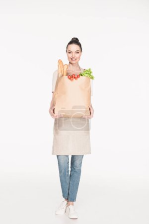 woman in apron holding paper package full of food isolated on white