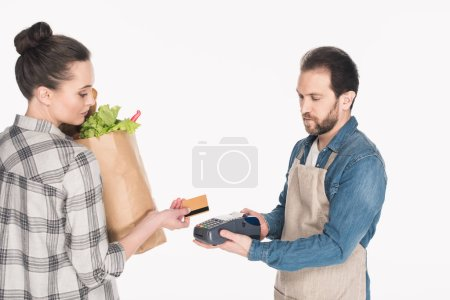 side view of woman with paper package with food giving credit card to shop assistant with cardkey reader isolated on white