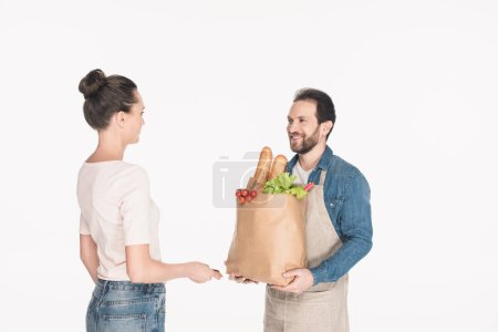 side view of woman giving credit card to shop assistant in apron with paper package full of food isolated on white