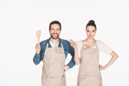 portrait of smiling couple in aprons with wooden kitchen utensils isolated on white