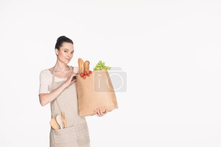 portrait of smiling woman with paper package full of food isolated on white