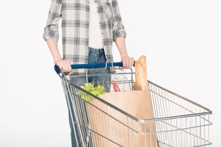 partial view of woman with paper package with grocery in shopping trolley isolated on white