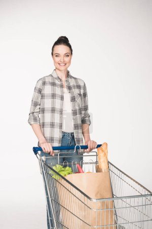 portrait of smiling woman with paper package full of food in shopping trolley isolated on white