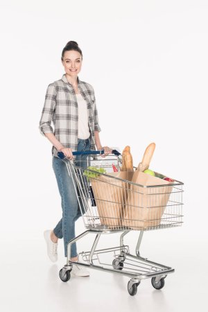 cheerful woman with paper packages in shopping cart isolated on white