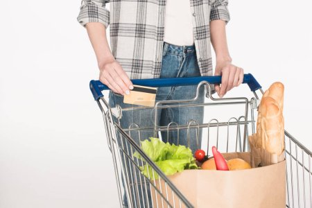partial view of woman with credit card in hand and paper package with grocery in shopping trolley isolated on white