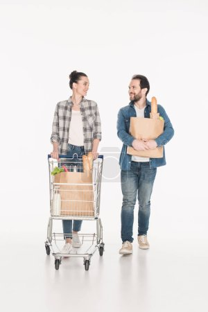 wife and husband with paper packages full of food and shopping trolley looking at each other isolated on white