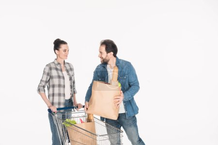 wife and husband with paper packages full of food and shopping trolley isolated on white
