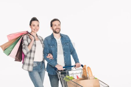 portrait of smiling couple with shopping bags and paper packages with grocery in shopping cart isolated on white