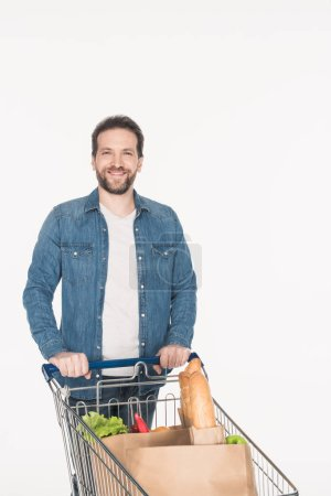 portrait of smiling man with shopping cart full of paper packages with food isolated on white