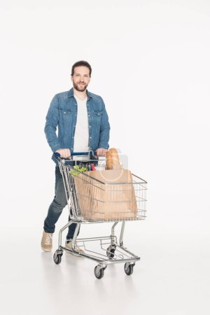 smiling man with shopping cart full of paper packages with grocery isolated on white