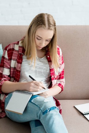 teen student girl writing in notebook while sitting on sofa and doing homework