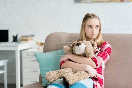 beautiful teen girl embracing her teddy bear while sitting on couch