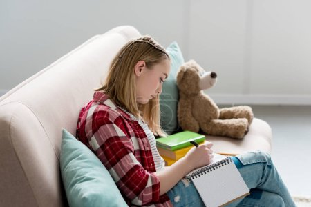 teen student girl writing in notebook while sitting on couch and doing homework