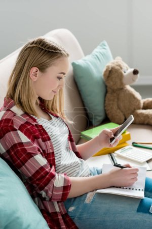 teen student girl doing homework on couch and using smartphone