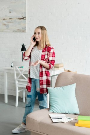 beautiful teen girl in red plaid shirt talking by phone at home