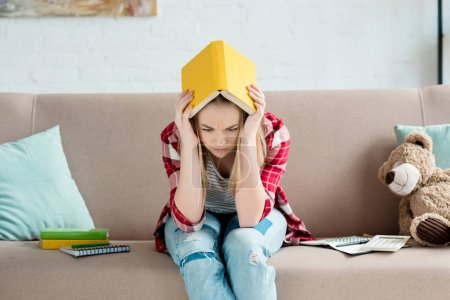 depressed teen student girl with book on head sitting on couch at home
