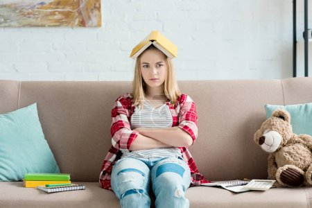 sad teen student girl with book on head sitting on couch at home and looking at camera