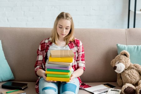 teen student girl with stack of books sitting on couch