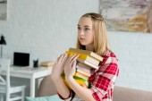 teen student girl with stack of books at home