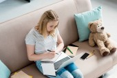 high angle view of teen student girl doing homework while sitting on couch