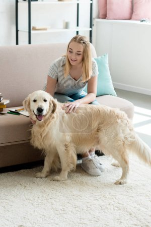 teen student girl petting her adorable golden retriever at home