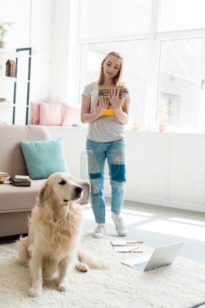 beautiful teen girl with stack of books studying at home with her golden retriever